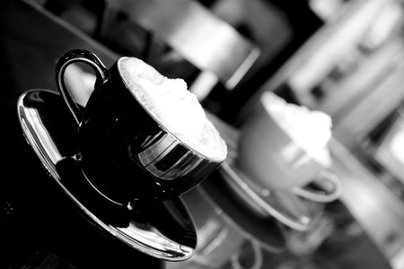 coffee table: two coffee cups with whipped cream, black and white