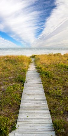 next horizon: boardwalk leading to beach with dramatic sky, vertical panorama
