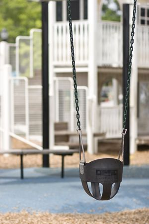 infant swing on playground in foreground, play equipment out of focus in background 版權商用圖片