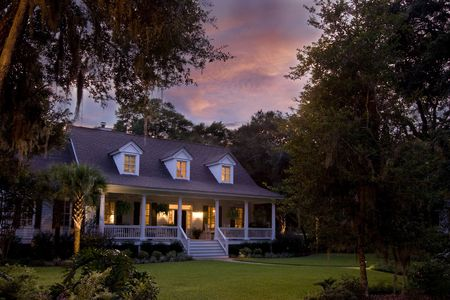 beautiful house lit up at twilight with orange clouds
