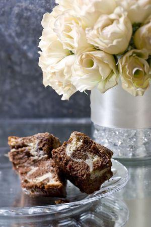 decedent: marbled brownies on glass plate with vase, shot with tilt shift lens.
