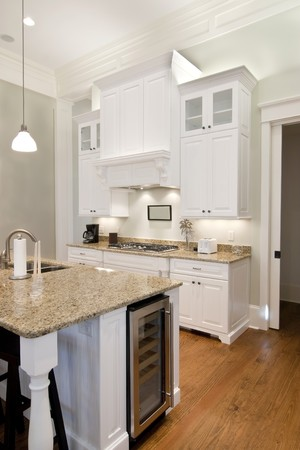 expensive granite: opulent white kitchen with granite countertops and wine fridge