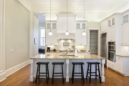 luxury eat-in kitchen with white cabinets and granite counters