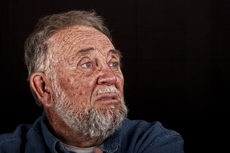 surly: very old man grieving over loss, over black Stock Photo