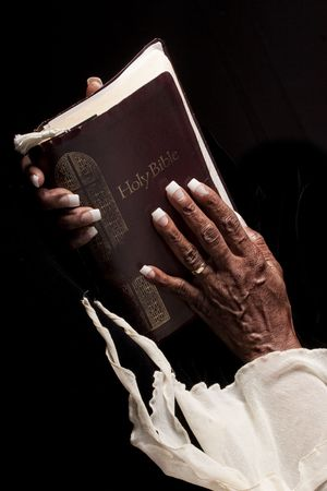african worship: bible being held by wrinkled african american hands