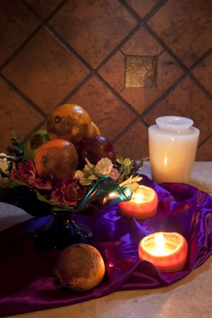 still life of rotten fruit in bowl and candles photo