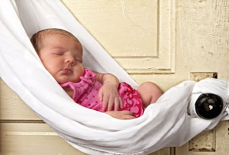 newborn baby sleeping in sling