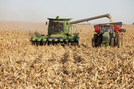 combine and tractor harvesting corn photo