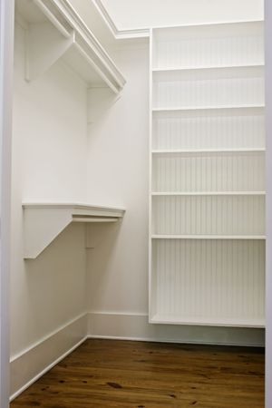 large white empty walk-in closet with shelves