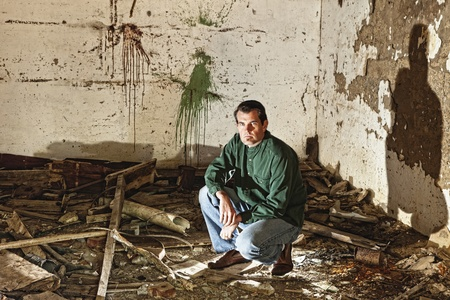 water damage: man among indoor ruins of home from natural disaster