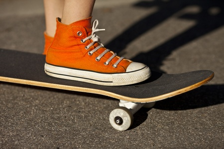 converse: orange shoe standing on skateboard