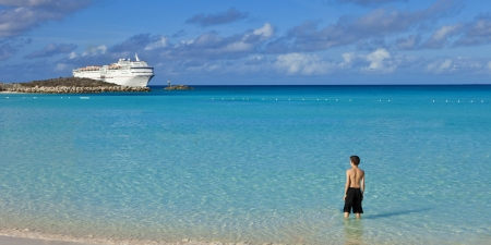 bahamian: boy standing on tropical bahamian beach with cruise ship in background