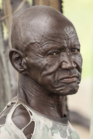 ontbering: PANWELL, SOUTH SUDAN-NOVEMBER 2, 2013: An unidentified man in the village of Panwell, South Sudan wears the expression of a life of hardship.