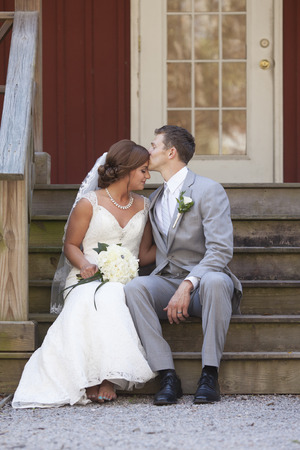 seated: Young newly married couple seated on steps, groom kissing bride on forehead