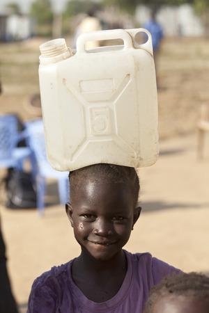 BOR、南スーダン-2010 年 12 月 3、: 正体不明の子供は彼女の頭の上大きい水コンテナーを運ぶ。