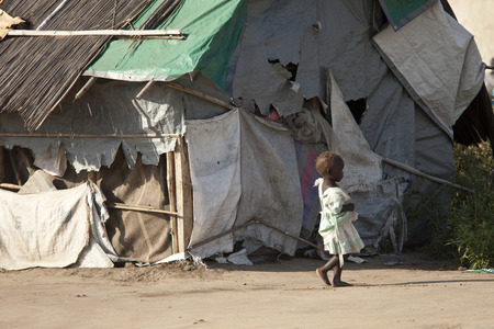 destitute: BOR, SOUTH SUDAN-DECEMBER 3 2010:Unidentified malnourished child walks past the shack she and her family live in in South Sudan