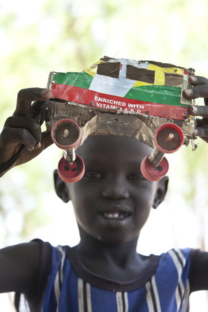 south sudan: BOR, SOUTH SUDAN, FEBRUARY 27 2013: Child makes creative use of garbage to make toys in South Sudan.