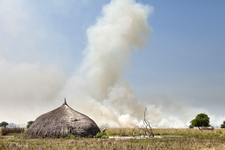 african village: grassfire burns in the distance with African village in foreground in South Sudan