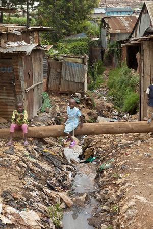 KIBERA, KENYA-DECEMBER 6, 2010: Unidentified children play near filthy water and garbage in Kibera, Africa's largest slum.