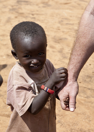 third eye: BISIL, KENYA-DECEMBER 7, 2010: An unidentified Maasai child holds an aid workers hand near the village of Bisil in southern Kenya