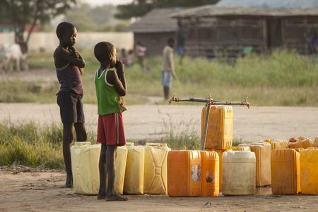pobreza: BOR, SUDÁN DEL SUR-01 de noviembre 2013: Los niños no identificados esperar a que el agua para encender en un punto central de agua en Bor, Sudán del Sur Editorial