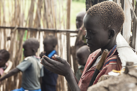 persecution: PANWELL, SOUTH SUDAN-NOVEMBER 2, 2013: An unidentified child prays in an outdoor church in South Sudan