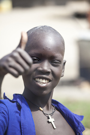BOR, SOUTH SUDAN-DECEMBER 2 2010: Unidentified Christian boy give the thumbs up. Christians were persecuted in South Sudan for decades Редакционное