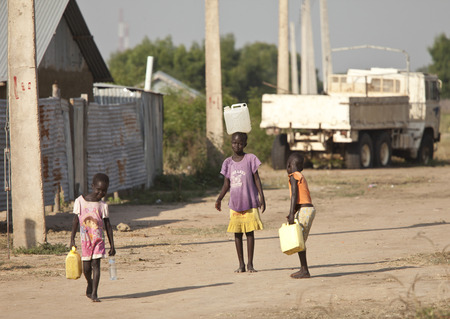 carrying: BOR, SOUTH SUDAN-DECEMBER 3 2010: Unidentified children carry containers of water back to their families.