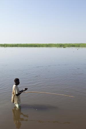 white nile: BOR, SUD�N DEL SUR-03 de diciembre 2010: el hombre no identificado peces en el r�o Nilo Blanco de Sud�n del Sur