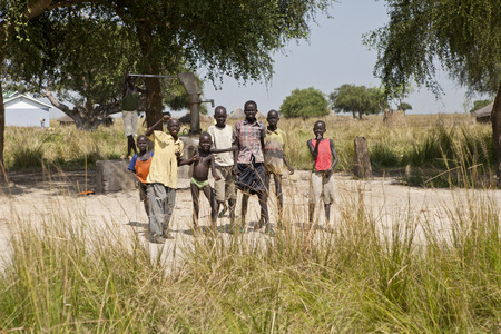 LILIIR, SOUTH SUDAN-DECEMBER 4, 2010: Unidentified children play around a water well in a rural village in South Sudan