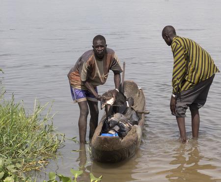 un p�cheur: BOR, SUD SOUDAN-26 juin 2012: les p�cheurs non identifi�s hisser un poisson hors de l'Canor � Bor, au Sud-Soudan.