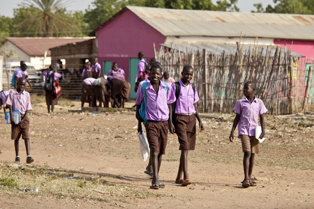 south african: TORIT, SOUTH SUDAN-FEBRUARY 20, 2013: Unidentified students in uniform leave school in South Sudan.