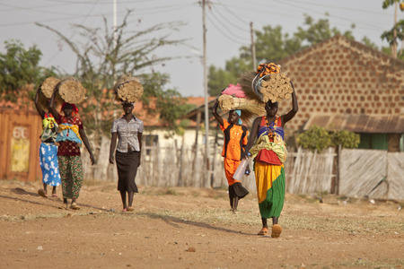 south africa soil: TORIT, SOUTH SUDAN-FEBRUARY 20, 2013: Unidentified women carry heavy loads on their heads in South Sudan