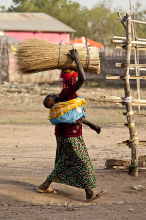 south africa soil: TORIT, SOUTH SUDAN-FEBRUARY 20 2013: Unidentified woman carries a heavy load on her head and her baby on her back in Torit, South Sudan Editorial