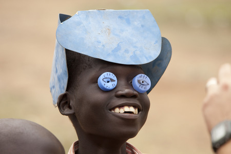 TORIT, SOUTH SUDAN-FEBRUARY 21 2013: An unidentified boy plays with a homemade mask and hat he made out of garbage in South Sudan