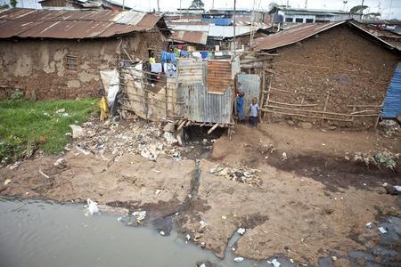 アフリカ最大のスラム街キベラの不潔な水の近くキベラ、ケニア-12 月 6, 2010年: 正体不明の子ども遊び。 報道画像