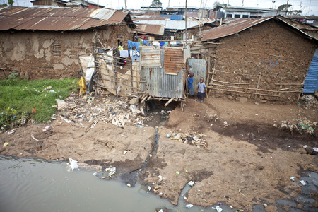 africa child: KIBERA, KENYA-DECEMBER 6, 2010: Unidentified children play near filthy water in Kibera, Africas largest slum.