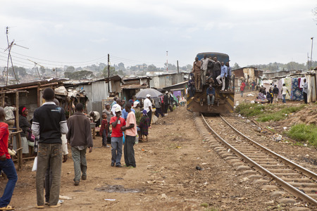 KIBERA, KENYA-DECEMBER 6 2010: Crowds of unidentified people engage in commerce and daily life in Kibera, Nairobi Kenya's largest slum as the train comes through.