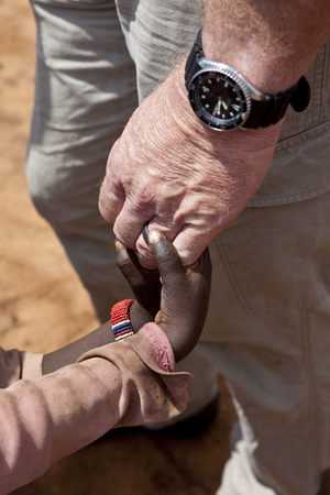 missionary: closeup of an aid workers hand as he holds the hand of two African children.