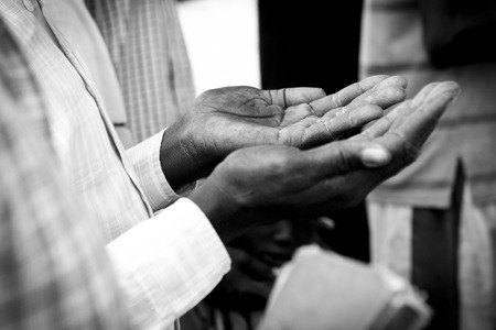 persecution: closeup of weathered hands of a man praying in South Sudan