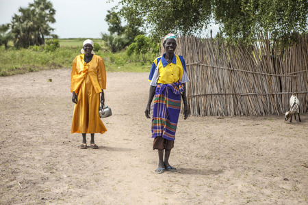 south africa soil: PANWELL, SOUTH SUDAN-NOVEMBER 2, 2013: Unidentified women in colorful dress go about their business in a small village in South Sudan Editorial