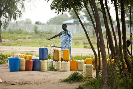 cholera: BOR, SOUTH SUDAN-JUNE 23, 2012: Unidentified people wait with containers for water in the village of Bor, South Sudan Editorial