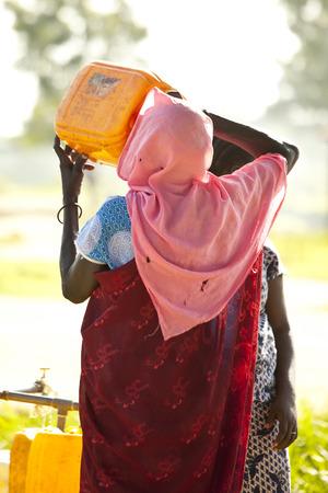 POBRES NI�OS: BOR, SUD�N DEL SUR-25 de junio 2012: Una mujer no identificados bebidas Sud�n del Sur desde una jarra de agua en un punto de llenado de agua central.