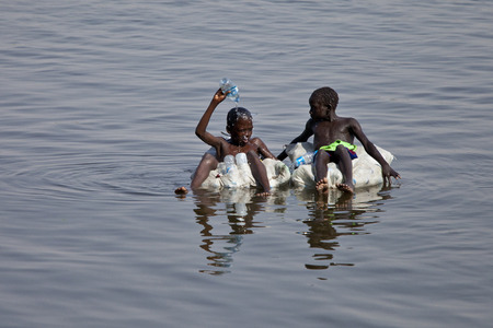 nile: JUBA, SOUTH SUDAN-FEBRUARY 19, 2013: Unidentified kids float down the Nile river on sacks filled with empty water bottles. Editorial