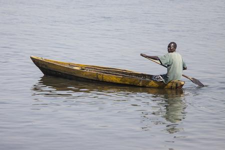 nile: JUBA, SOUTH SUDAN-FEBRUARY 19 2013: unidentified man paddles traditionally made canoe on the White Nile through Juba, capital of South Sudan