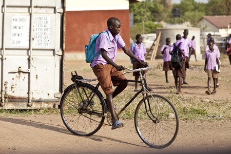 TORIT, SOUTH SUDAN-FEBRUARY 20, 2013: Unidentified schoolboy rides his bicycle from school in South Sudan Editöryel