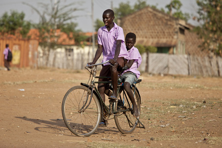 south africa soil: TORIT, SOUTH SUDAN-FEBRUARY 20, 2013: Unidentified schoolboys ride their bike from school in South Sudan Editorial