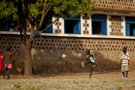 africa child: TORIT, SOUTH SUDAN-FEBRUARY 20, 2013: An unidentified group of kids play football in a village in South Sudan Editorial