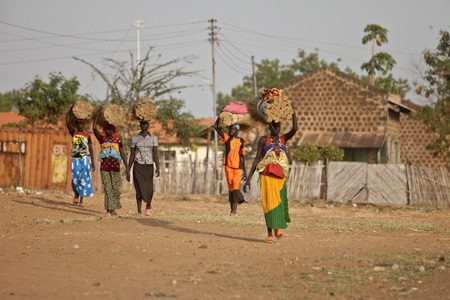 TORIT, SOUTH SUDAN-FEBRUARY 20 2013: Unidentified women carry heavy loads on their heads in Torit, South Sudan Editorial