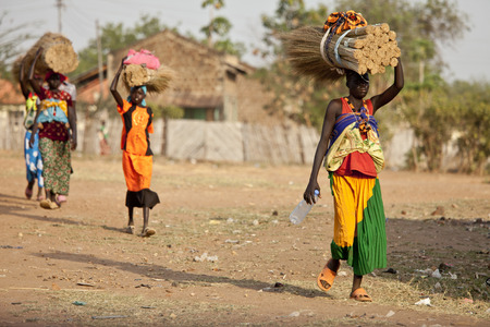 TORIT, SOUTH SUDAN-FEBRUARY 20 2013: Unidentified women carry heavy load on their heads in Torit, South Sudan. Editorial